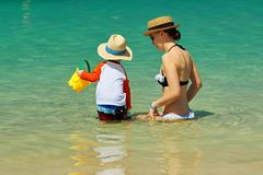 Niño de dos años que juega con la madre en la playa Imagenes de archivo