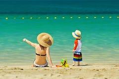Niño de dos años que juega con la madre en la playa Fotografía de archivo libre de regalías