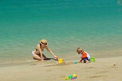 Niño de dos años que juega con la madre en la playa Fotos de archivo