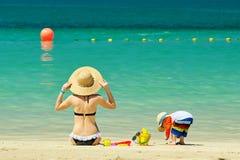 Niño de dos años que juega con la madre en la playa Fotografía de archivo