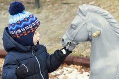 Niño de dos años que juega con un caballo del juguete Niño que alimenta el caballo de madera imagenes de archivo