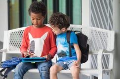 Niño de dos muchachos que se sienta en banco y que juega al juego en la tableta en el presc imagenes de archivo