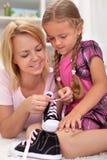 Niño de enseñanza de la madre cómo atar los zapatos Fotos de archivo libres de regalías