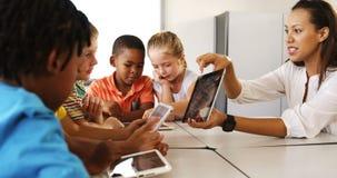Niño de enseñanza del profesor en la tableta digital en biblioteca