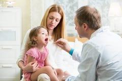 Niño de examen del pediatra imagenes de archivo