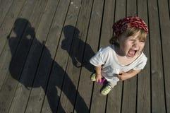Niño de griterío. muchacha dulce con un genio Fotografía de archivo libre de regalías