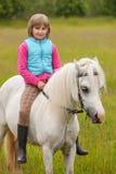 Niño de la chica joven que se sienta a horcajadas en un caballo blanco Imagen de archivo libre de regalías