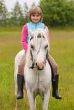 Niño de la chica joven que se sienta a horcajadas en un caballo blanco Foto de archivo