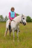 Niño de la chica joven que se sienta a horcajadas en un caballo blanco Fotografía de archivo