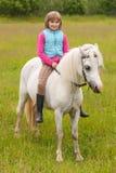 Niño de la chica joven que se sienta a horcajadas en un caballo blanco Imagenes de archivo