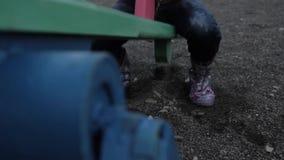 Niño de la inocencia que balancea en un oscilación en patio abandonado del ` s de los niños almacen de video