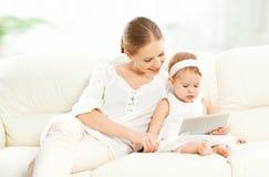 Niño de la madre y del bebé con la tableta en el sofá en casa Imagen de archivo
