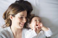 Niño de la madre y del bebé en una cama blanca fotos de archivo libres de regalías