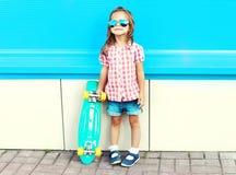 Niño de la moda con el monopatín en la ciudad Fotos de archivo