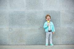 Niño de la moda con la piruleta cerca de la pared gris Fotografía de archivo