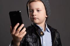 Niño de la moda con un teléfono celular Foto de archivo libre de regalías