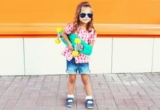 Niño de la moda - niño elegante de la niña con las gafas de sol que llevan del monopatín en ciudad Foto de archivo