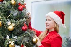 Niño de la muchacha alrededor del árbol de navidad el Nochebuena Foto de archivo