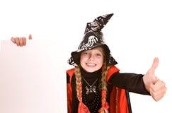 Niño de la muchacha de la bruja de Víspera de Todos los Santos con la bandera y el pulgar. Fotos de archivo