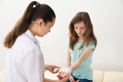 Niño de la muchacha del doctor Bandaging Hands Of Imágenes de archivo libres de regalías