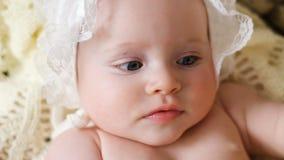 Niño de la muchacha desnudo en un casquillo blanco que miente en la cesta almacen de metraje de vídeo