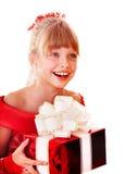 Niño de la muchacha en alineada roja con el rectángulo de regalo. Imagenes de archivo