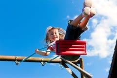 Niño de la muchacha en el oscilación en el jardín Imágenes de archivo libres de regalías