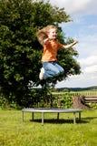Niño de la muchacha en el trampolín en el jardín Fotos de archivo libres de regalías