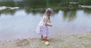 Niño de la muchacha en la orilla de una charca metrajes