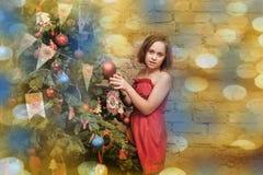 Niño de la muchacha en vestido rojo en el árbol de navidad Foto de archivo
