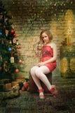 Niño de la muchacha en vestido rojo en el árbol de navidad Imagenes de archivo