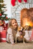 Niño de la muchacha que celebra una feliz Navidad en casa por el fireplac foto de archivo