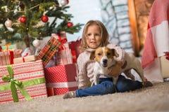 Niño de la muchacha que celebra una feliz Navidad en casa por el fireplac imagenes de archivo