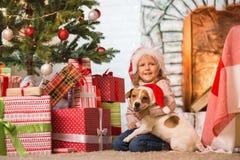 Niño de la muchacha que celebra una feliz Navidad en casa por el fireplac imágenes de archivo libres de regalías