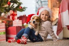 Niño de la muchacha que celebra una feliz Navidad en casa por el fireplac foto de archivo libre de regalías