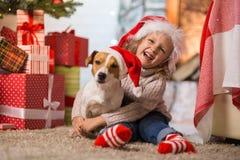 Niño de la muchacha que celebra una feliz Navidad en casa por el fireplac fotografía de archivo libre de regalías