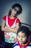 Niño de la muchacha que se coloca con las manos dobladas con su hermano foto de archivo libre de regalías