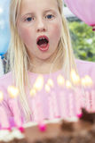 Niño de la muchacha que sopla hacia fuera velas de la torta de cumpleaños imagenes de archivo