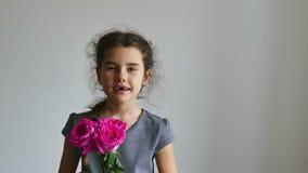 Niño de la muchacha que sostiene un ramo de rosa de la flor interior almacen de video