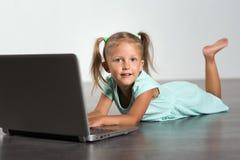 Niño de la niña con el ordenador portátil fotos de archivo
