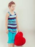 Niño de la niña con la almohada roja de la forma del corazón Imagen de archivo libre de regalías