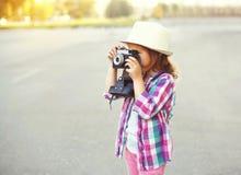 Niño de la niña con la cámara retra que hace foto Fotografía de archivo