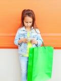 Niño de la niña con los panieres usando smartphone Imagen de archivo