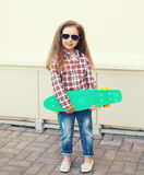 Niño de la niña de la moda con el monopatín en ciudad Imagenes de archivo