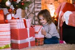 Niño de la niña en casa por la chimenea y los wi del árbol de navidad foto de archivo libre de regalías