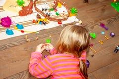 Niño de la niña que juega con las porciones de juguetes plásticos coloridos en piso de madera dentro fotografía de archivo