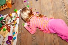 Niño de la niña que juega con las porciones de juguetes plásticos coloridos en piso de madera dentro imagen de archivo