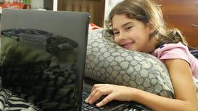 Niño de la niña que juega en el ordenador portátil del juego online del cuaderno almacen de metraje de vídeo