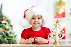 Niño de la niña que lleva un sombrero rojo festivo de Papá Noel Imágenes de archivo libres de regalías