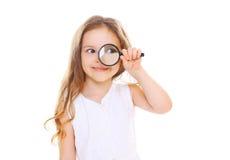 Niño de la niña que mira a través de una lupa en blanco Imagenes de archivo